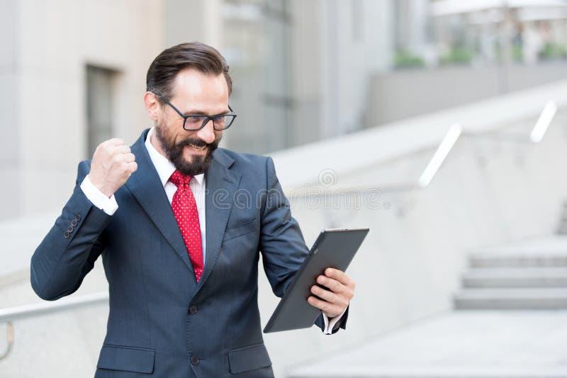Verärgerter bärtiger Geschäftsmann kleidete in der blauen Klage an, die mit der Faust tablet während der Videokonferenz aus Büro  lizenzfreie stockfotos