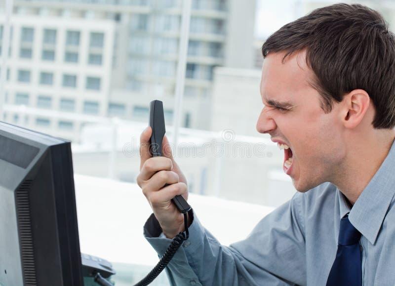 Verärgerter Büroangestellter am Telefon lizenzfreies stockfoto