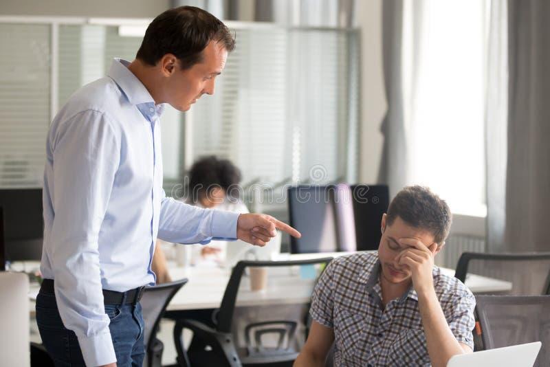 Verärgerter Chef, der inkompetenten männlichen Büroangestellten an w rügend schilt stockbilder