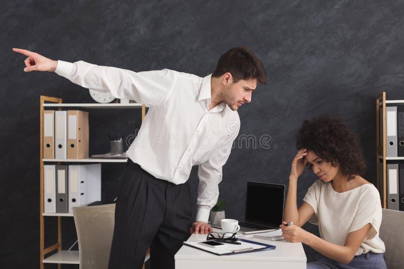 Verärgerter Chef, der seinen behilflichen Sekretär feuert stockfotos