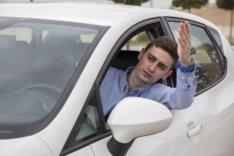 Verärgerter Fahrer fest am Stau, der äußeres Auto aufpasst stockfotos