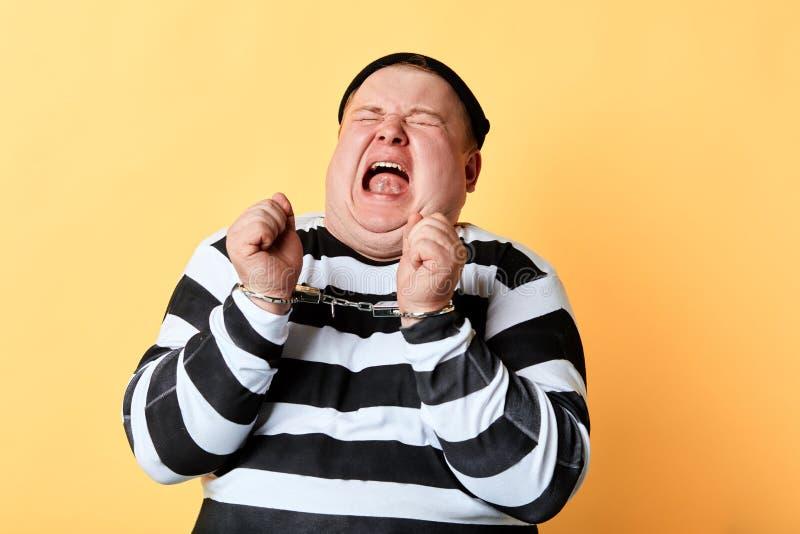 Verärgerter frustrierter Dieb beim Handschellenschreien stockfoto