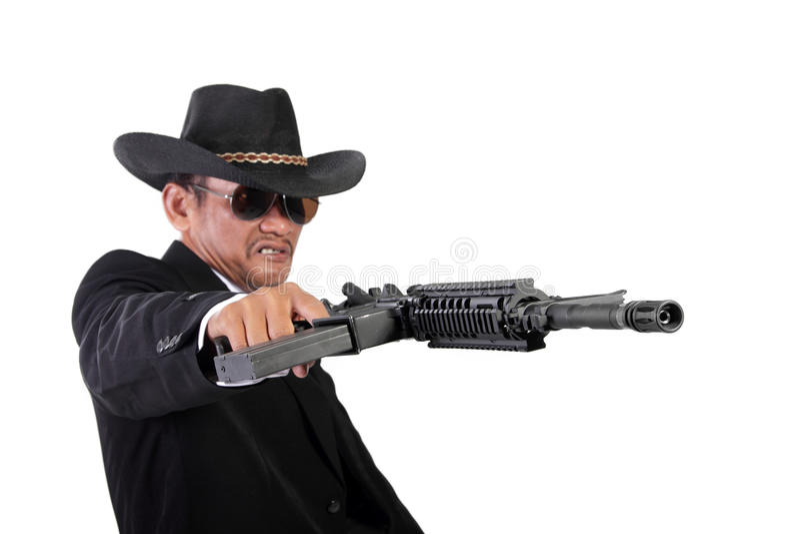 Verärgerter Gangster, der maniacally sein Gewehr abfeuert lizenzfreie stockbilder