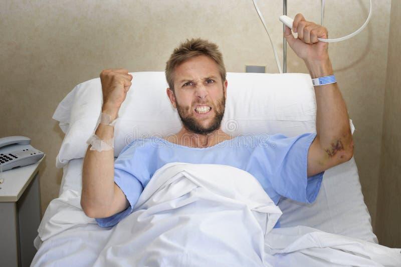 Verärgerter geduldiger Mann am Krankenhauszimmer, das im Bett drückt das Krankenschwesteranruf-Knopfgefühl nervös und umgekippt l lizenzfreie stockfotos