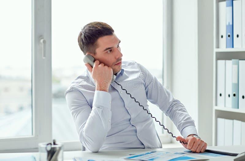 Verärgerter Geschäftsmann, der um Telefon im Büro ersucht stockfotografie