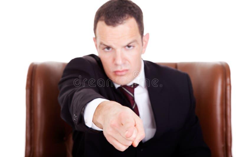 Verärgerter Geschäftsmann gesetzt auf einem Stuhl, zeigend lizenzfreies stockbild