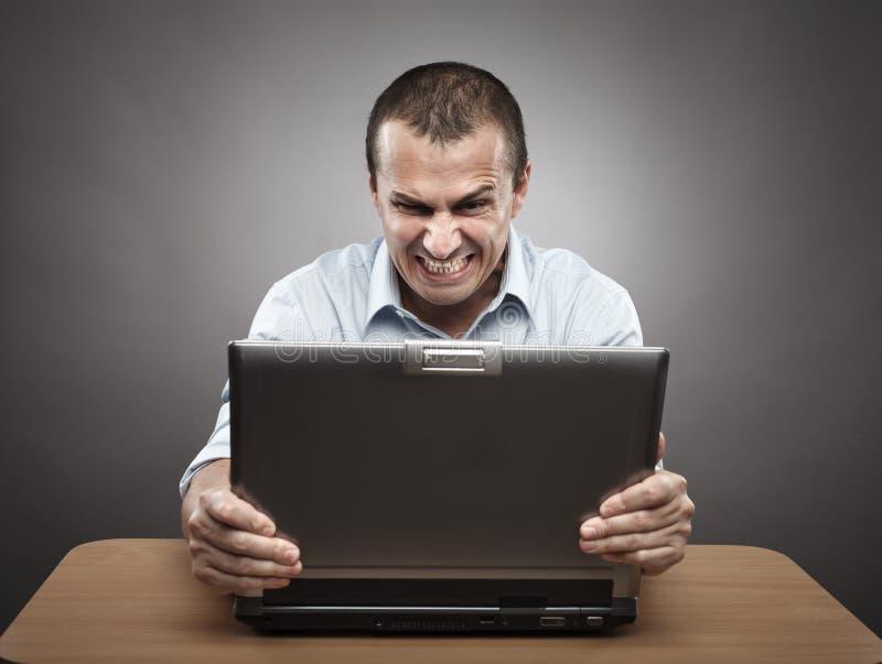 Verärgerter Geschäftsmann am Laptop lizenzfreie stockfotografie