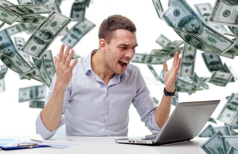 Verärgerter Geschäftsmann mit Laptop und fallendem Geld stockbild