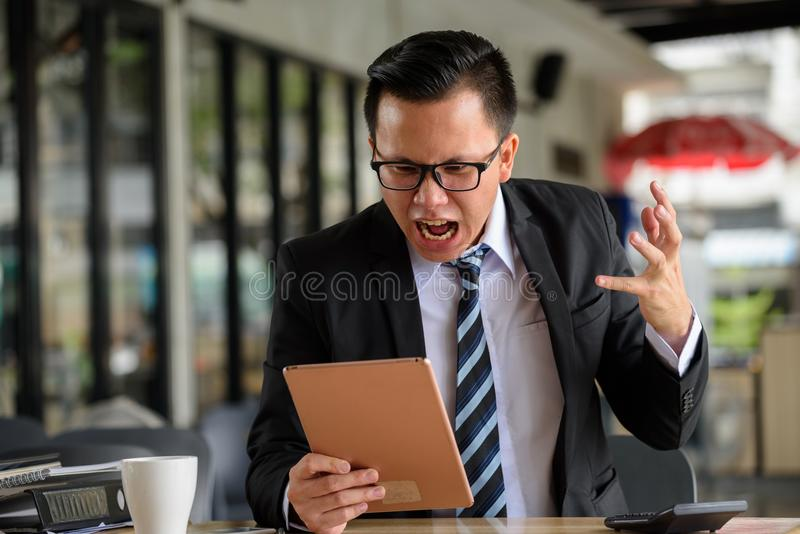 Verärgerter Geschäftsmann sehen schlechte Nachrichten durch Tablette stockfoto