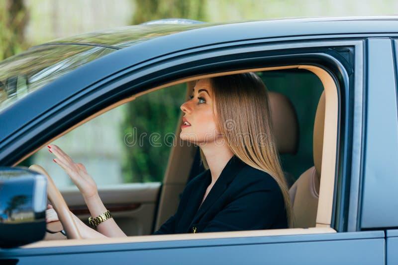 Verärgerter Gestenblick des Mädchens auf hinterem Spiegel stockfoto