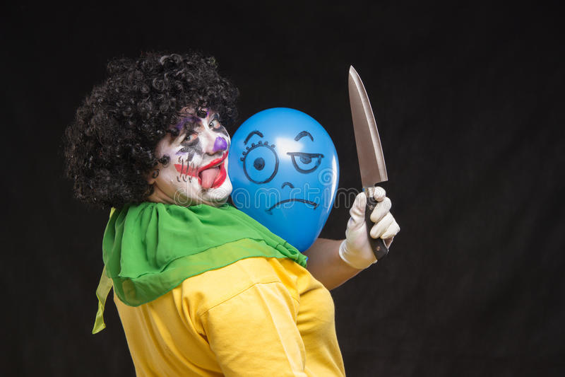 Verärgerter hässlicher Clown möchte einen Ballon in der Kappe töten lizenzfreie stockbilder