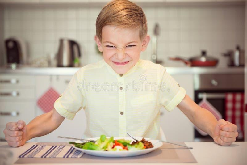 Verärgerter hungriger Junge, der auf dem Tisch seine Faust schlägt lizenzfreies stockfoto