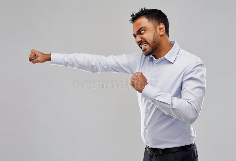 Verärgerter indischer Geschäftsmann, der über Grau kämpft lizenzfreies stockfoto