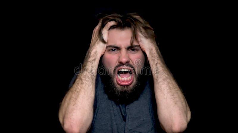 Verärgerter junger Mann, der, die negativen Gefühle ausdrückend schreit und heraus zerreißen sein Haar, lokalisiert auf schwarzem stockbild