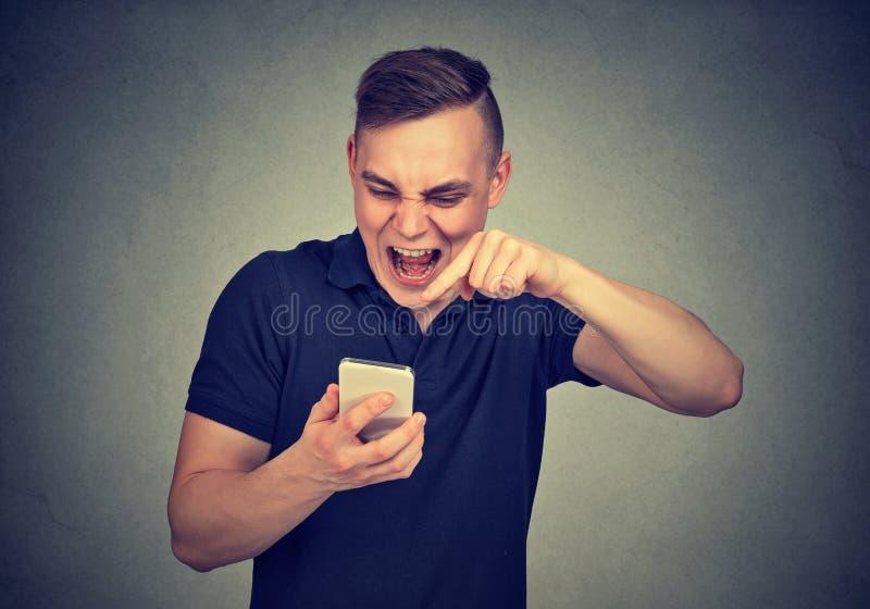Verärgerter junger Mann, der am Handy schreit stockfotografie