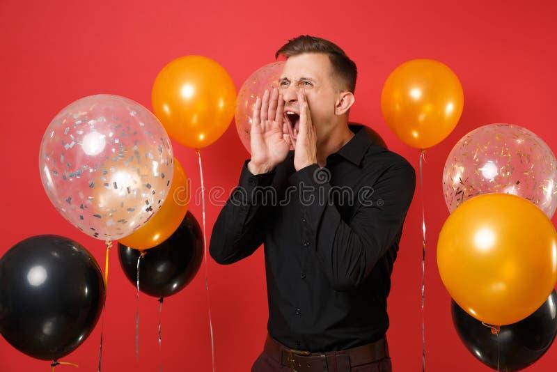 Verärgerter junger Mann im schwarzen klassischen Hemdschreien, Hände nahe Mund auf roten Hintergrundluftballonen halten Valentins stockfotos