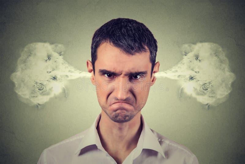 Verärgerter junger Mann, Schlagdampf, der aus Ohren herauskommt lizenzfreies stockfoto