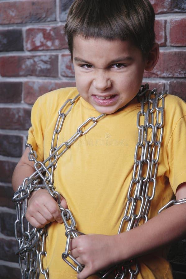 Verärgerter Kindgefangener mit Kette stockbild