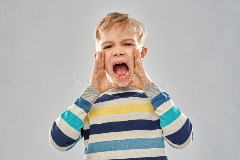 Verärgerter kleiner Junge in gestreiftem Pullover schreiend lizenzfreies stockfoto