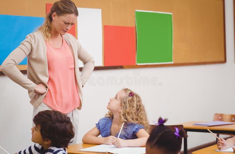 Verärgerter Lehrer, der Schüler mit den Händen auf Hüften schaut lizenzfreie stockfotos