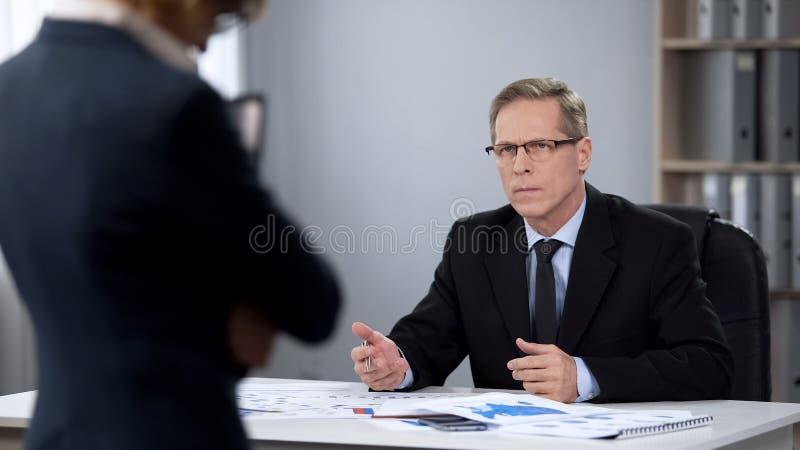 Verärgerter männlicher Direktor betrachtet Assistenten, Beschäftigungsbeendigung, schwache Leistung stockbild