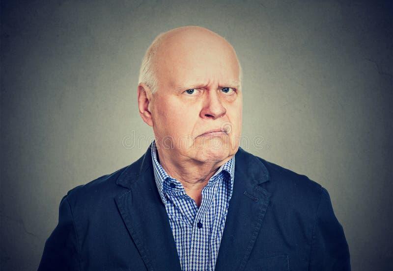 Verärgerter, mürrischer älterer Geschäftsmann, lokalisiert auf grauem Hintergrund lizenzfreies stockfoto
