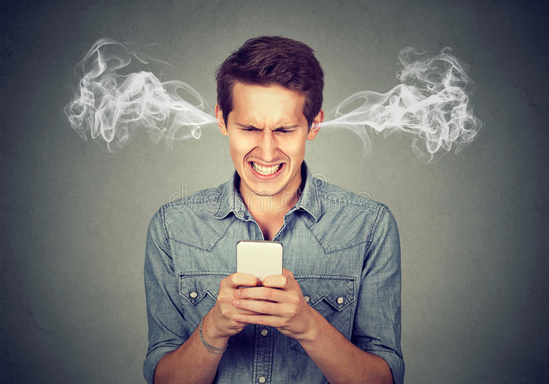Verärgerter Mann, der eine Textnachricht auf dem Schlagdampf des Smartphone herauskommt aus Ohren liest stockfoto