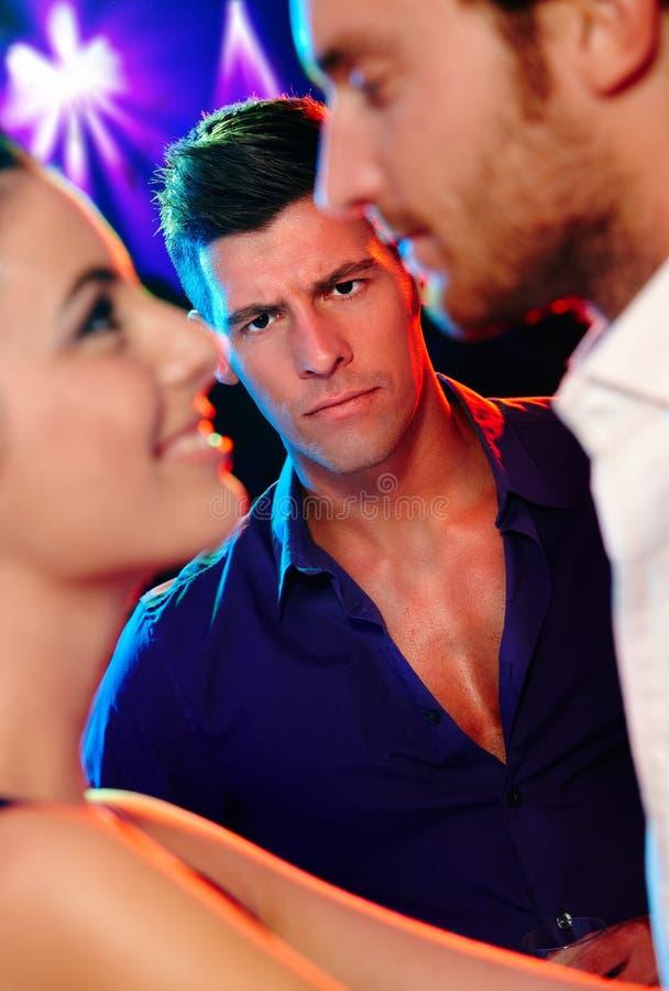 Verärgerter Mann, der liebevolle Paare im Nachtklub betrachtet lizenzfreie stockfotos