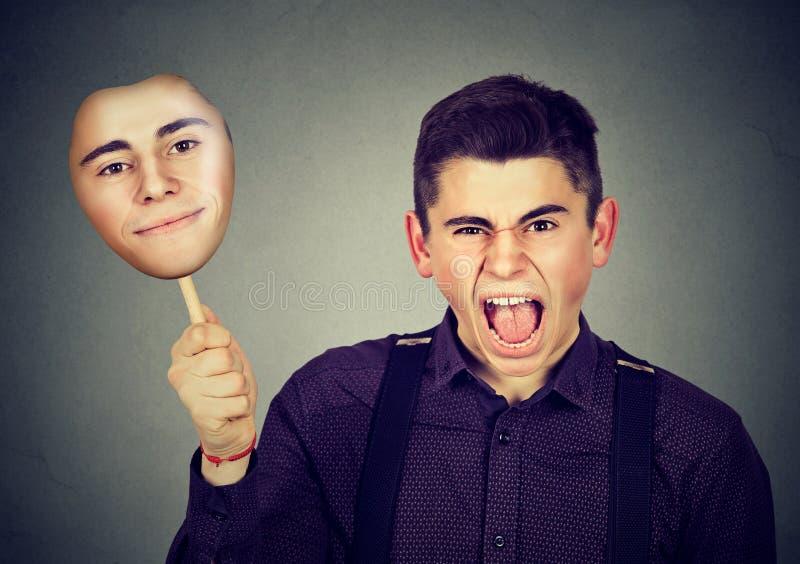 Verärgerter Mann, der Maske mit ruhigem Gesichtsausdruck entfernt stockfotos