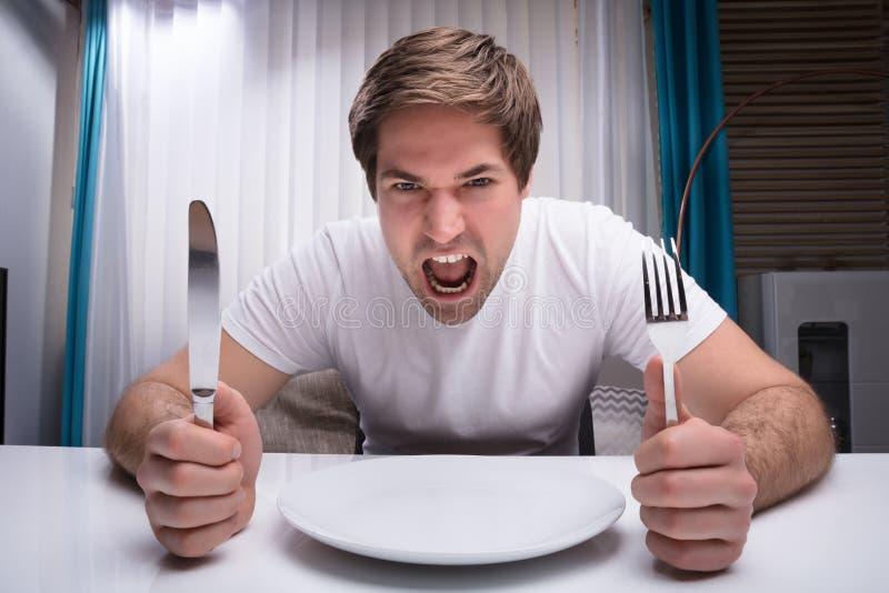 Verärgerter Mann, der Messer und Gabel hält stockfotos