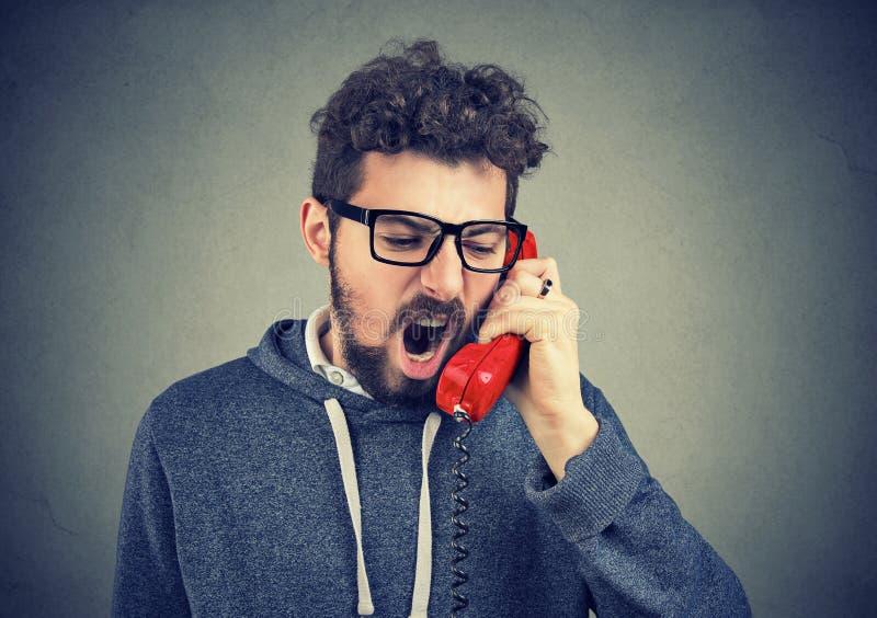 Verärgerter Mann, der am Telefon schreit stockbilder