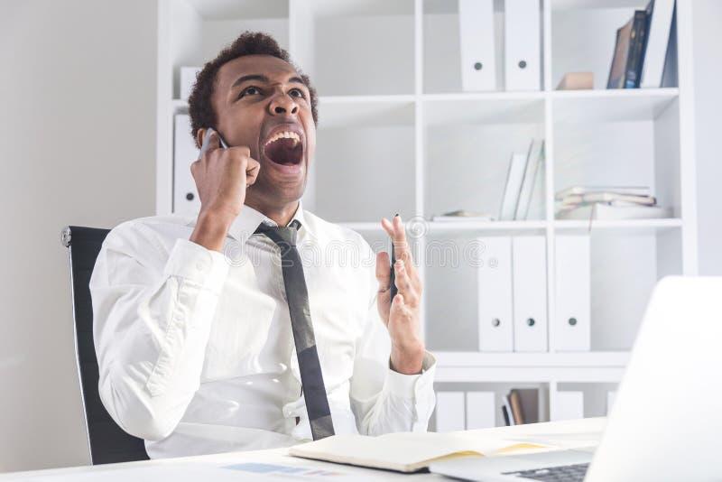 Verärgerter Mann, der am Telefon schreit stockfotografie