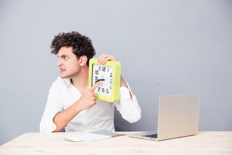 Verärgerter Mann, der am Tisch sitzt und auf Uhr zeigt stockbilder