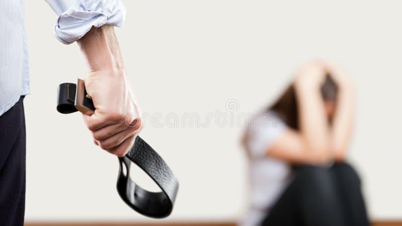 Verärgerter Mann hob die Hand an, die Ledergürtel über Wandecke sitt hält stockbilder