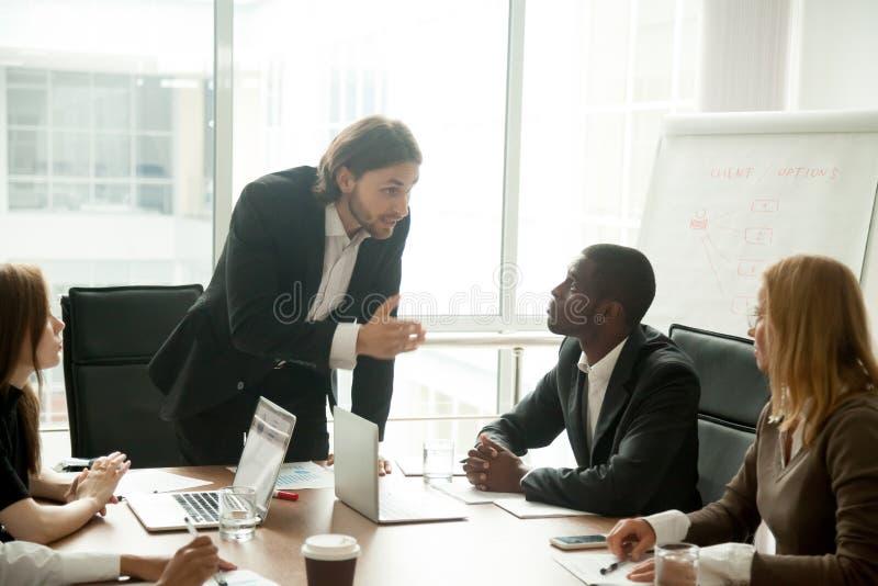 Verärgerter mittlerer Chef, der Angestellten für schlechte Arbeit bei der Sitzung schilt stockbilder