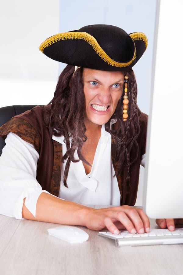 Verärgerter Pirat, der Computer verwendet lizenzfreie stockbilder