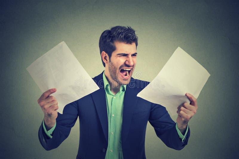 Verärgerter schreiender Geschäftsmann mit Dokumenten tapeziert Schreibarbeit stockfotos