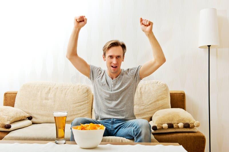 Verärgerter schreiender Mann, während das Aufpassen im Fernsehen zur Schau trägt stockfotografie