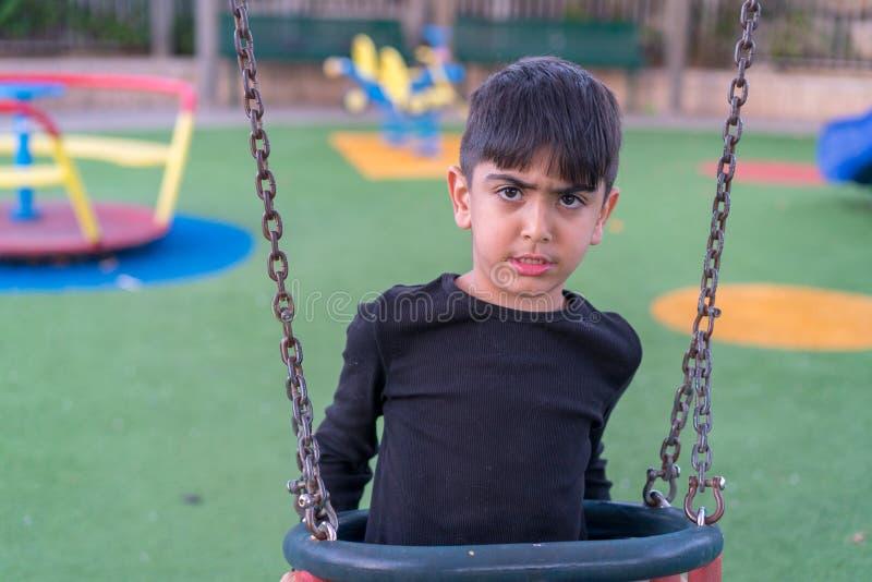Verärgerter trauriger Junge, der auf Schwingen sitzt stockfoto