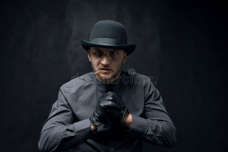 Verärgerter und aggressiver Mann mit einem Zahnstocher in seinem Mund, gegen einen dunklen Hintergrund stockfoto