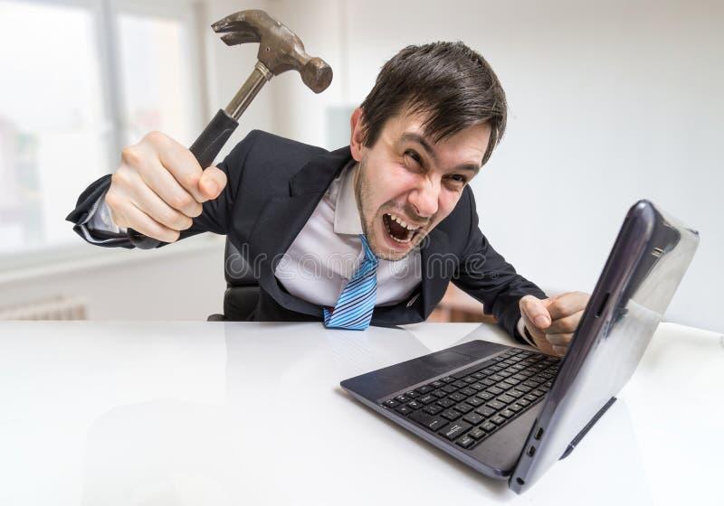 Verärgerter und verrückter Mann arbeitet mit Laptop Er wird Notizbuch mit Hammer beschädigen lizenzfreie stockbilder