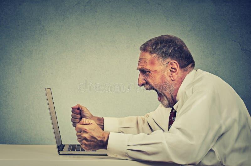 Verärgerter wütender älterer Geschäftsmann, der an dem Computer, schreiend arbeitet lizenzfreies stockfoto