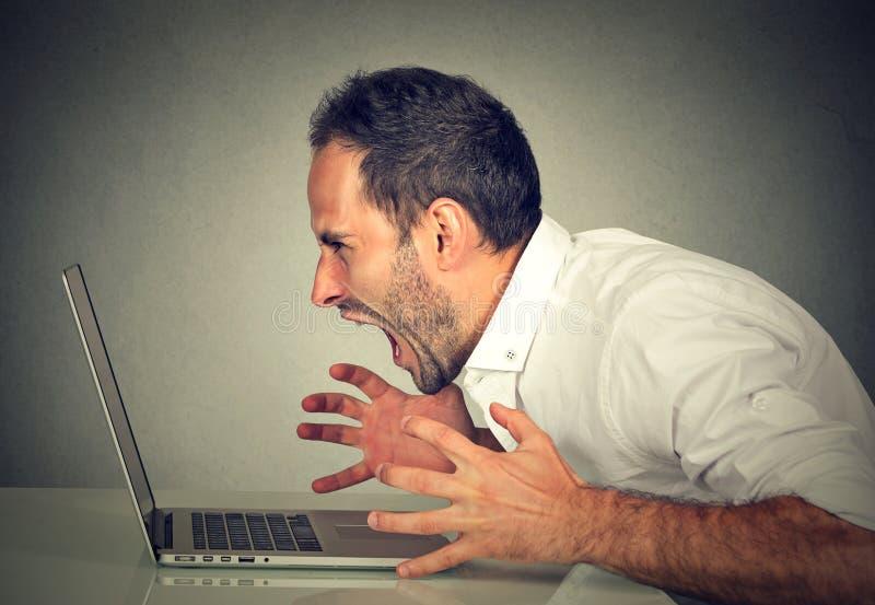 Verärgerter wütender Geschäftsmann, der am Computer schreit stockbilder
