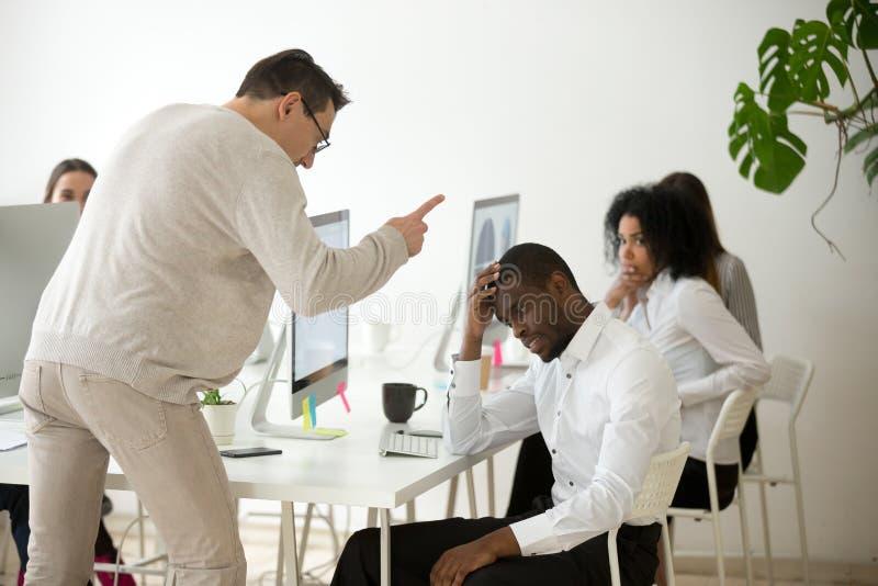 Verärgerter weißer Chef, der inkompetenten schwarzen Angestellten herein rügend schilt stockfoto