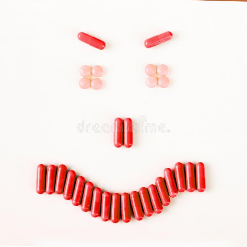 Verärgertes Lächeln gemacht von vielen Pillen und von Kapseln Wellnesskonzept stock abbildung