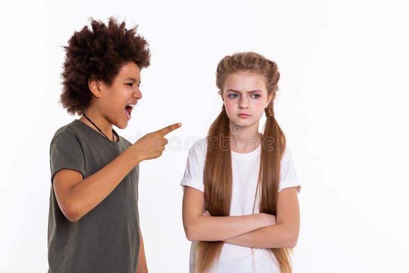Verärgertes langhaariges Mädchen, das entschlossen Hände während Junge zeigt auf sie kreuzt lizenzfreie stockfotos