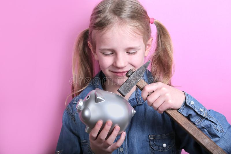 Verärgertes lustiges junges Mädchen mit silbernem Sparschwein und Hammer auf rosa Hintergrund Außer Geldkonzept stockbild