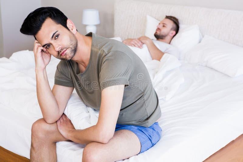 Verärgertes Paarhomosexuelles im Schlafzimmer stockfotografie