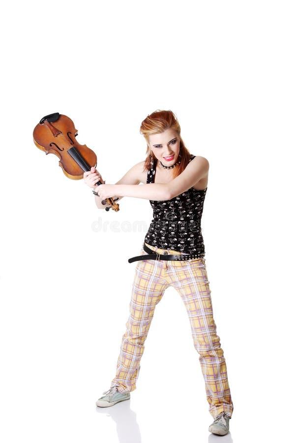 Verärgertes Punkmädchen, das beabsichtigt, ihre Geige zu brechen. lizenzfreies stockfoto