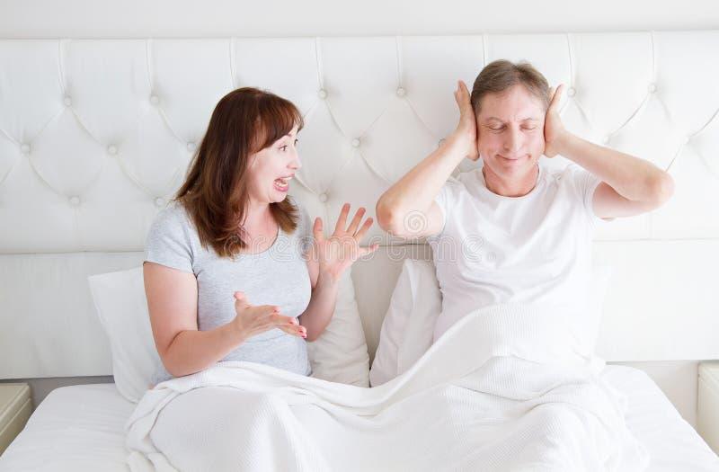 Verärgertes Schreien der kaukasischen Mittelalterfamilien-Paare im Bett Konflikt-Verhältnis-Konzept Ehemannabdeckungsohren durch  stockfotos